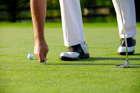 Golfer repair green with pitchfork