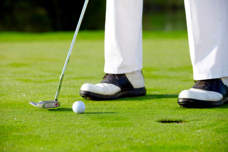 Golfer on green is putting Stock Photo