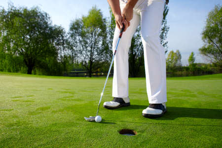 with holes: Golfer on green is putting Stock Photo