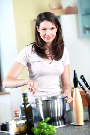 stir: Young woman is cooking pasta Stock Photo