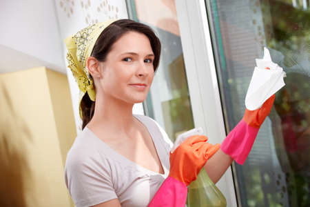 housecleaning: Young woman is cleaning a window