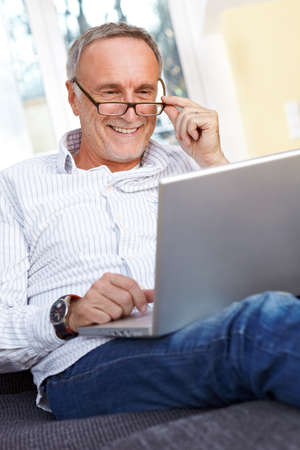 old people smiling: Senior man with laptop at home