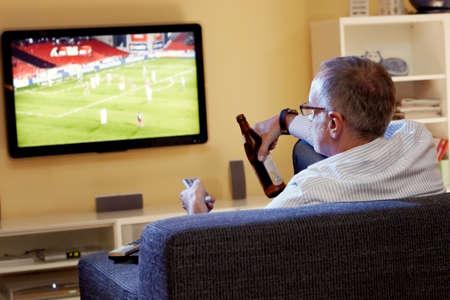 Senior man kijkt voetbal op tv