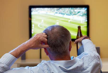 テレビでサッカーを見ている年配の男性 写真素材