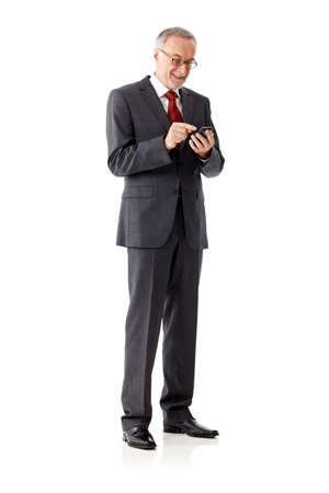 mature businessman: Standing mature business man with smart phone, isolated Stock Photo