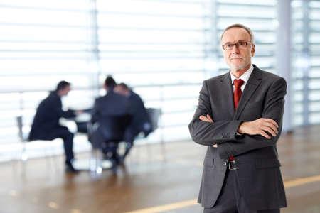 patron: Hombre de negocios mayor con los brazos cruzados, el equipo en el fondo