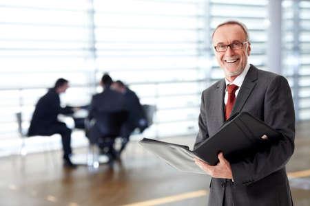 Senior business man met map, team op de achtergrond Stockfoto