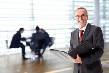 contend: Senior business man with folder, team in the background Stock Photo