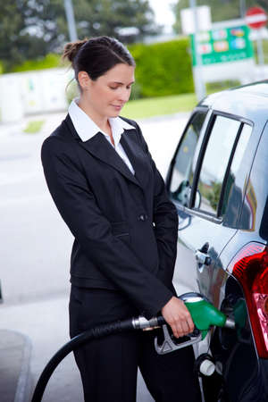 petrol station: Business woman  fills gas at petrol station