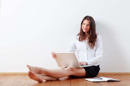 床に座ってラップトップを持つ若い女性
