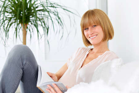 mid age: Woman with book on the sofa Stock Photo