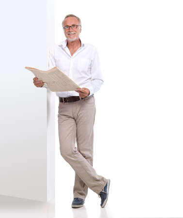 mature male: Mature man leaning against a wall and reading newspaper