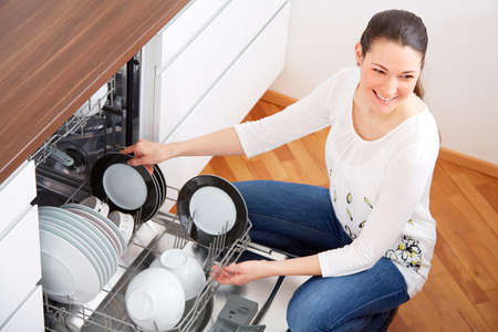 emty: Young woman emty out the dishwasher