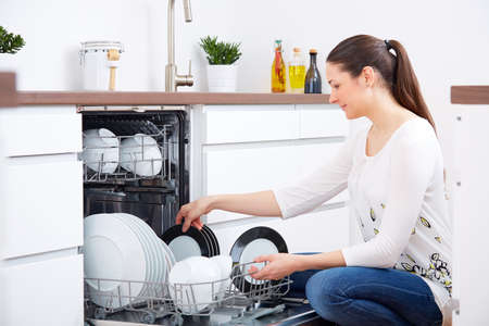 dishwasher: Young woman emty out the dishwasher