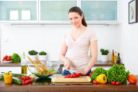 Young woman prepare salad in the kitchen photo