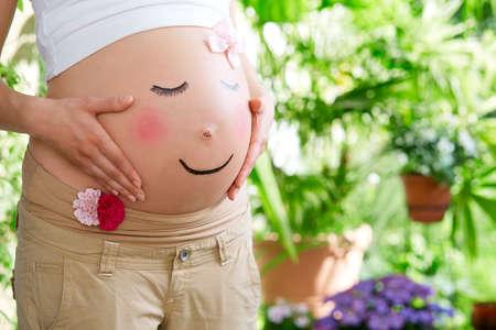 Schwangeren Bauch als ein Gesicht gemalt Standard-Bild - 40392085