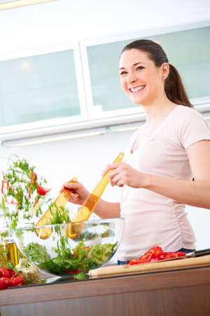 Young woman in the kitchen prepare salad photo