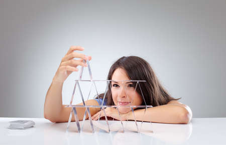 instability: Young woman is building a house of cards