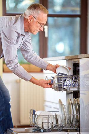 bright housekeeping: Senior man empty out the dishwasher