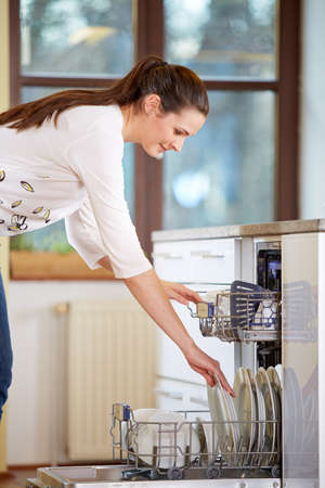 bright housekeeping: Young woman empty out the dishwasher