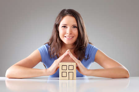 contend: Young smiling woman make a roof with hands symbolical