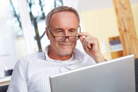 ノート パソコンとメガネと年配の男性 写真素材