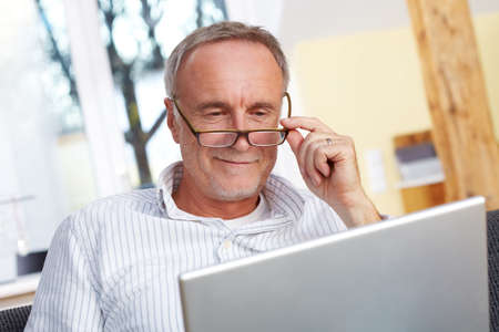 retirement age: Senior man with laptop and glasses