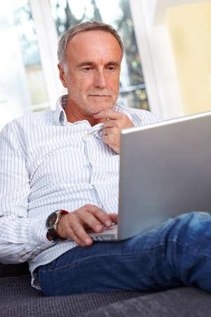 persona pensando: Hombre mayor con la computadora portátil en casa