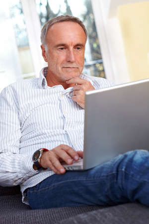 person computer: Senior man with laptop at home