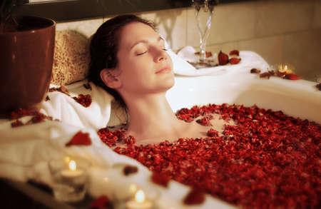 descansando: Mujer que se relaja en la bañera con flores color de rosa