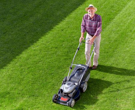 잔디 깎는 기계가있는 성숙한 정원사 스톡 콘텐츠