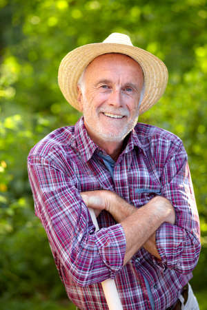 red straw: Mature gardener with straw hat