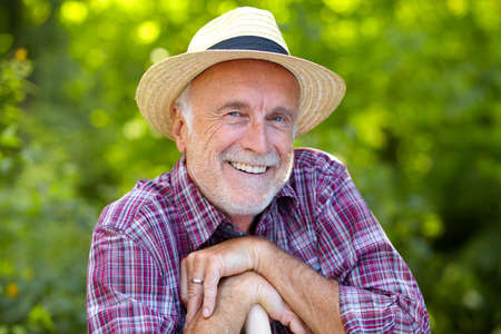Happy senior gardener with straw hat Stockfoto