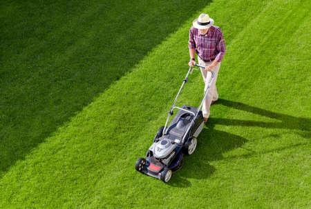 Mowing senior man with straw hat in the garden Standard-Bild