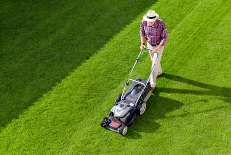 Mowing senior man with straw hat in the garden Stock Photo