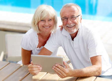 mujeres mayores: Diferente pareja de edad utilizando un Tablet PC al aire libre en la piscina Foto de archivo