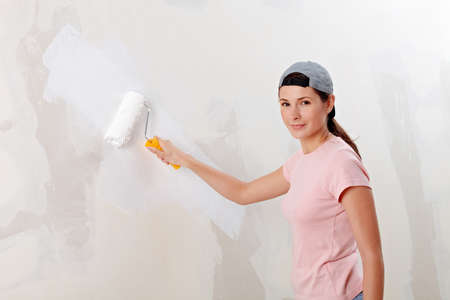 craftswoman: Young woman decorate her new flat with white paint