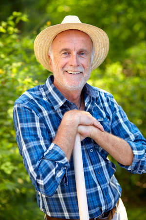 彼の庭で麦わら帽子とハッピー シニア庭師。