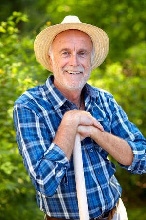 Happy senior gardener with straw hat in his garden.