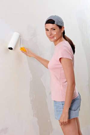 Young woman decorate wall in new flat, paint droplet in her face