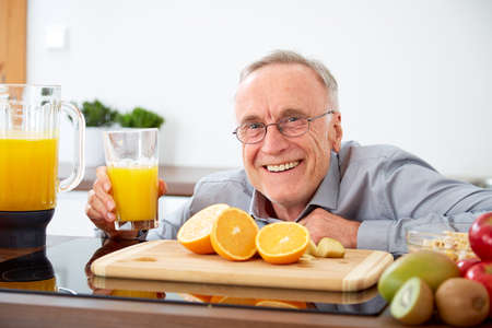 orange juice: Senior man with a glass of orange juice in the kitchen
