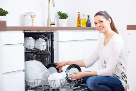 dishwasher: Smiling 20s woman in kitchen, empty out the full dishwasher Stock Photo
