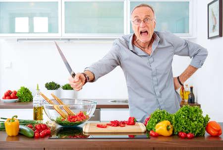cuchillo de cocina: hombre maduro agresiva en la cocina con el cuchillo Foto de archivo