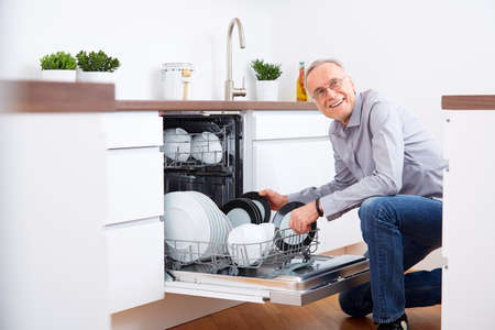 dishwasher: Senior man in the kitchen, empty out the dishwasher