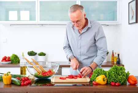 houseman: Mature man in the kitchen prepare salad Stock Photo