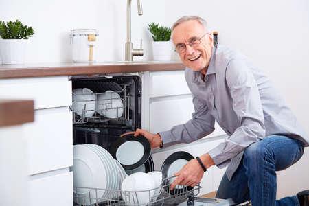 Lterer Mann, der in der Küche, entleeren Sie den Geschirrspüler Standard-Bild - 46632883