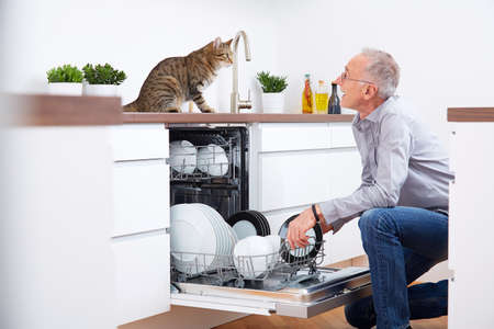 Senior man with cat in kitchen, empty out the dishwasher