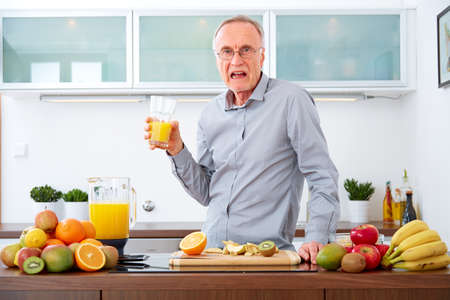 Senior man in the kitchen does not like fruits and juice