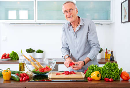 Mature man in the kitchen prepare salad Stock Photo