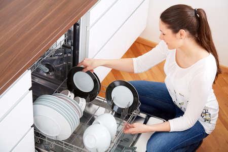 bright housekeeping: 20s woman in kitchen, empty out the full dishwasher